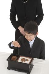 お焼香をする喪服姿の母親と息子