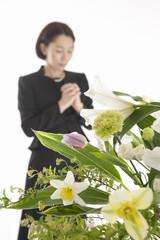 手を組んで祈る喪服姿の女性と祭壇の花