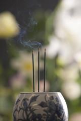 香炉で焚かれた三本の線香と花