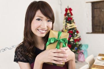 クリスマスプレゼントを抱える若い女性