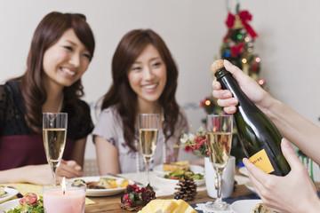 クリスマスパーティーでシャンパンを開ける
