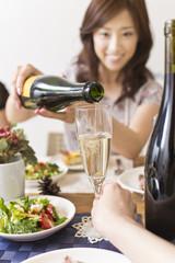 クリスマスパーティーでシャンパンを注ぐ