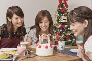 クリスマスケーキを見つめる女性三人
