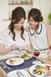 デジタルカメラで料理の写真を撮る女性二人