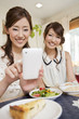 スマートフォンで料理の写真を撮る女性二人