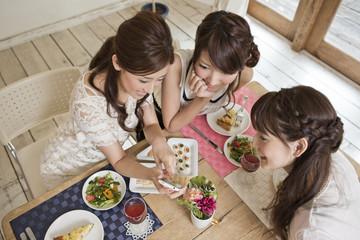 女子会でスマートフォンを見る女性三人