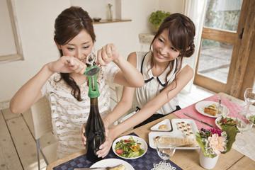 ワインの栓を開ける女性二人