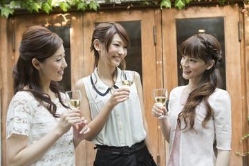 テラスでワインを飲む女性三人