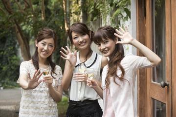 ワイングラスを持ち手を振る女性三人