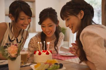 バースデーケーキを見つめる女性三人