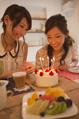 バースデーケーキを見つめる女性二人
