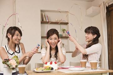 パーティーでクラッカーを鳴らす女性三人