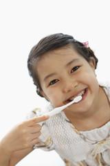 歯磨きをする笑顔の女の子