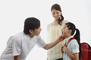 歯科医師に口を開けて見せる女の子と母親
