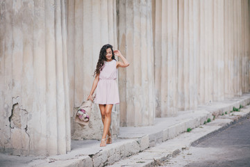 beautiful girl with a bouquet of peonies near old columns