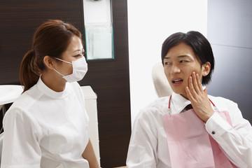 歯痛の相談をする若い男性と歯科医師