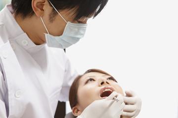 若い女性の歯科検診を行う歯科医師