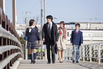並んで歩く中年男女と学生