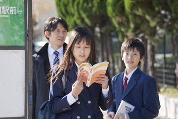 バス停で参考書を読む学生