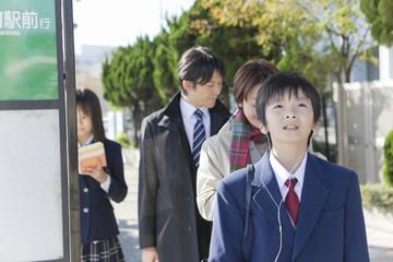 イヤホンを付けてバス停に立つ男子中学生