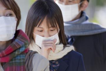 マスクを着けて並ぶ女子高校生
