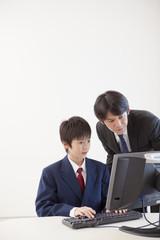 パソコンの指導をする教師と男子中学生