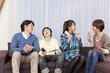 テレビゲームで遊ぶ学生と両親