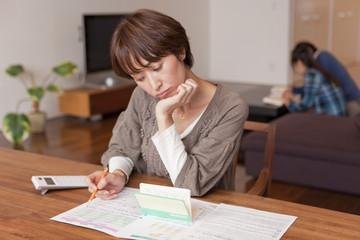 通帳と家計簿を眺めて考える中年女性