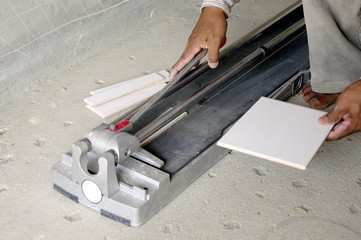 worker cut tiles with machine