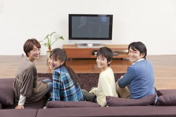 ソファに座って振り向く学生と両親