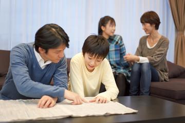 リビングで団欒する学生と両親