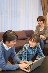 パソコンを一緒に楽しむ女子高校生と両親
