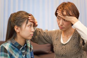 女子高校生の娘の熱を確認する母親