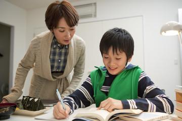 勉強する男子中学生と夜食を運ぶ母親