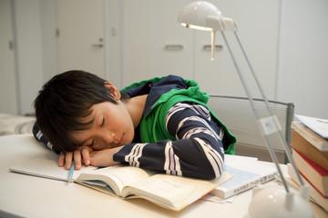 勉強に疲れてうたた寝をする男子中学生
