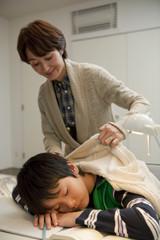 居眠りする男子中学生に上着を掛ける母親