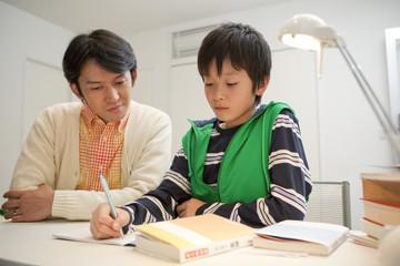勉強する男子中学生と指導する父親