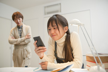 スマートフォンを操作する女子高校生