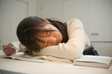 勉強に疲れてうたた寝をする女子高校生