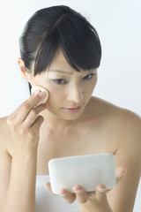 ファンデーションを塗る日本人女性
