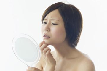 鏡を見て顔をしかめる日本人女性