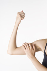 握りこぶしを作った上腕を触る日本人女性