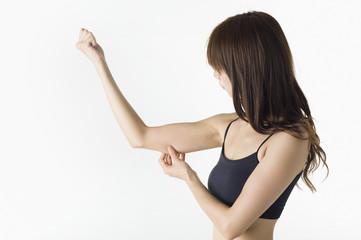 二の腕を摘んで見る日本人女性