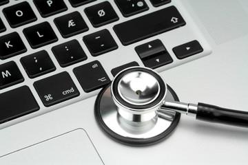 Stethoscope on the keyboard of pc, macro image.
