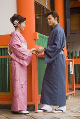 互いの手を繋いで向き合う和服姿の男女