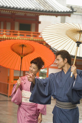 蛇の目傘を差して神社の境内を歩く和服姿の男女