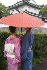 一本の蛇の目傘に二人で入る和服姿の男女