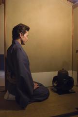 鉄瓶の前に正座する和服姿の男性