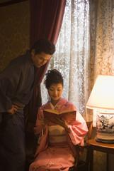 読書をする和服姿の女性と隣に立つ男性