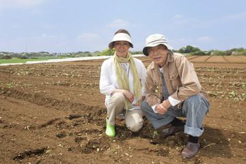 畑の中に座るシニアカップル